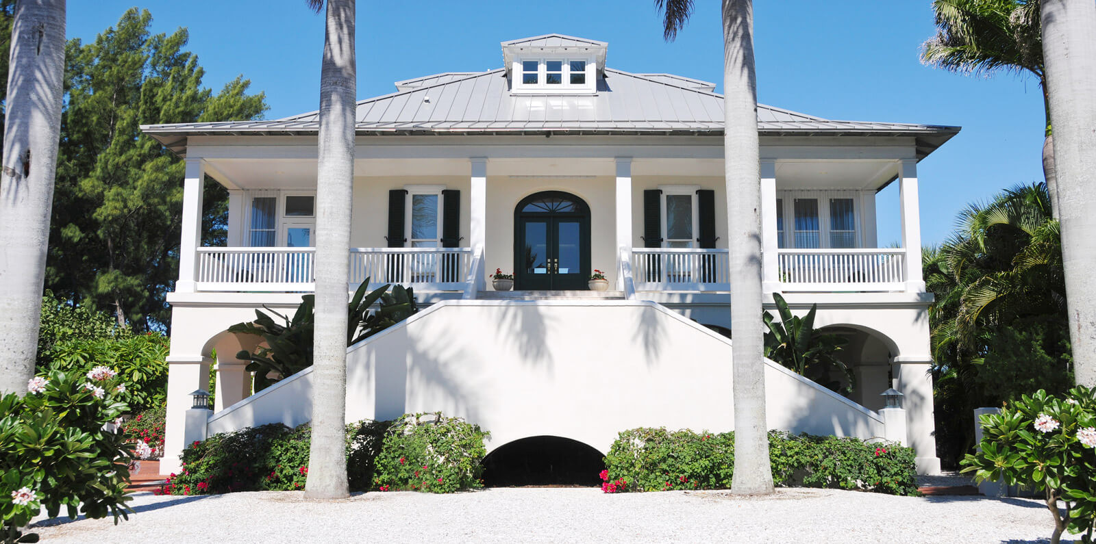 A beautiful white home with a metal roof and palms in the front yard